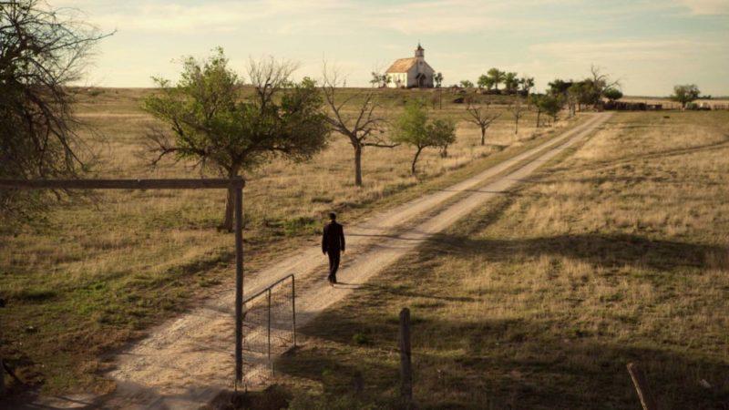 Eine Kirche steht in der Ferne einer verlassenen Ortschaft. Custer (Dominic Cooper) ist auf dem Weg in die Kirche.