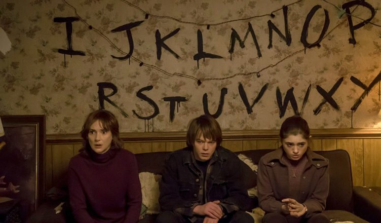 Stranger Things Joyce (Winona Ryders) Jonathan (Charlie Heaton) und Nancy (Natalia Dyers) sitzen auf einem Sofa