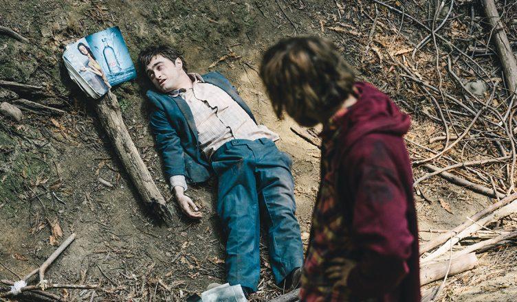 Daniel Radcliffe liegt als Manny am Boden und betrachtet ein Pinup-Magazin während Hank ihn betrachtet