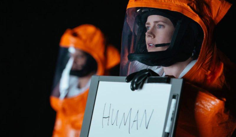 """Amy Adams als Louise hält ein Schild mit dem Wort """"Human"""" in """"Arrival"""" (2016)"""