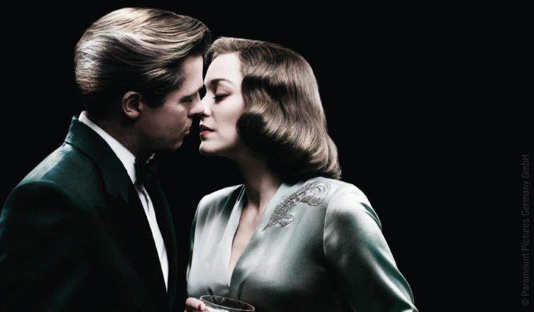 Marion Cottillard und Brad Pitt stehen in Abengarderobe vor einem schwarzen Hintergrund - ihre Gesichter berühren sich liebevoll