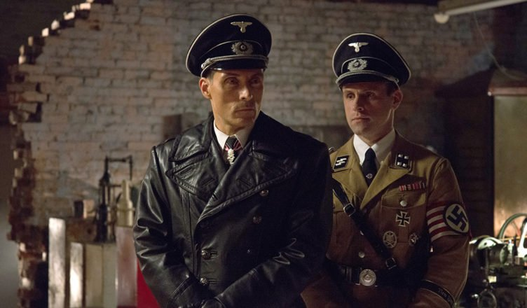 SS-Obersturmbannführer John Smith steht in voller Uniform in der Serie The Man in the High Castle - Staffel 1stramm. Hinter ihm ein Kollege.
