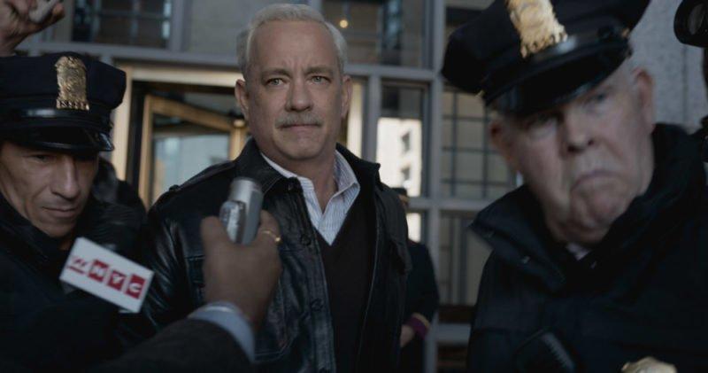 Tom Hanks als Sully wird interviewt und von Polizisten eskortiert in Sully
