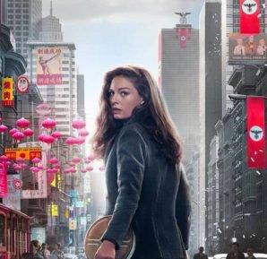 Juliana Crain gespielt von Alexa Davalos mit einer Filmrolle zwischen einem japanischen Häuserblock zur Linken und einem Nazi-Häuserblock zur Rechten auf Poster zu The Man in the High Castle.