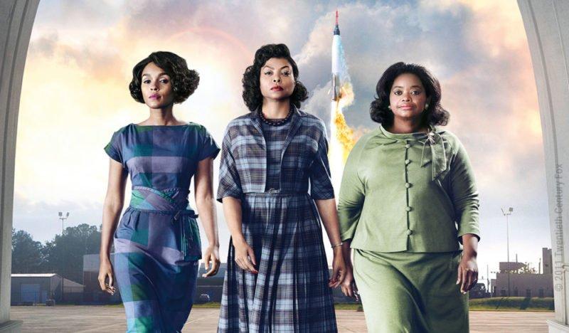 Die drei Heldinnen des Dramas Hidden Figures – Unerkannte Heldinnen laufen selbstbewusst geradeaus während hinter ihnen eine Rakete startet