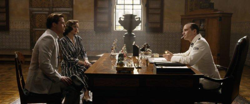 Brad Pitt, Marion Cotillard und August Diehl sitzen am Schreibtisch des deutschen Offiziers in Allied