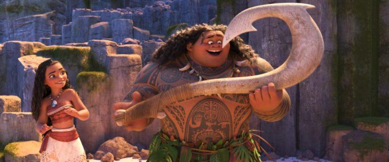 Vaiana und Maui stehen am Strand, während Maui seinen magischen Haken betrachtet.