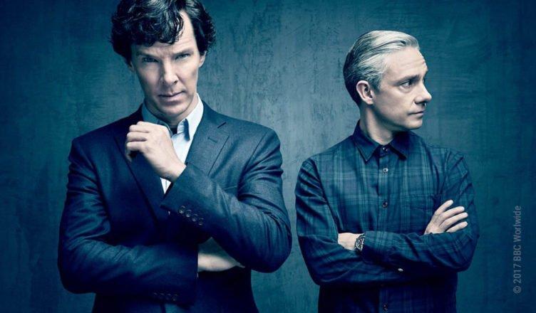Sherlock Holmes und Dr Watson stehen vor einer grauen Steinwand