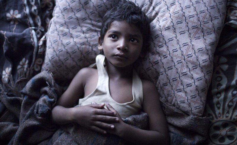 Saroo (Sunny Pawar) liegt in einem Bett in Film Lion