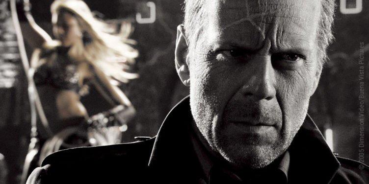 Schwarz-Weiß-Aufnahme: Bruce Willis im Vordergrund und Jessica Alba unscharf im Hintergrund in Sin City