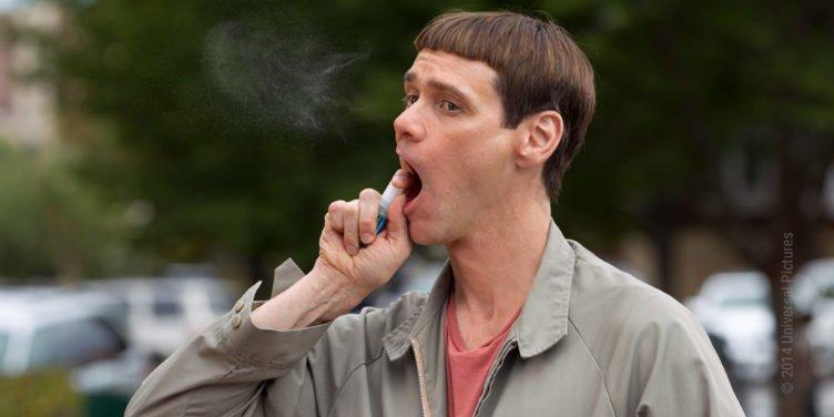 Jim Carrey hantiert mit einer Spraydose in seinem Mund herum in Dumm und Dümmer