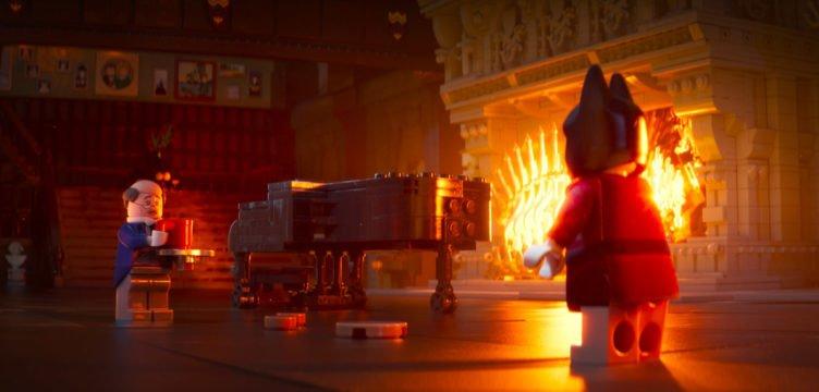 Bruce Wayne und Butler Alfred unterhalten sich in einem Saal mit brennendem Kamin in The Lego Batman Movie