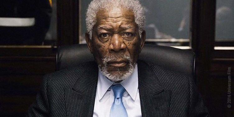 Morgan Freeman sitzt in Anzug an einem Tisch und schaut verdutzt und ängstlich zu gleich in London Has Fallen