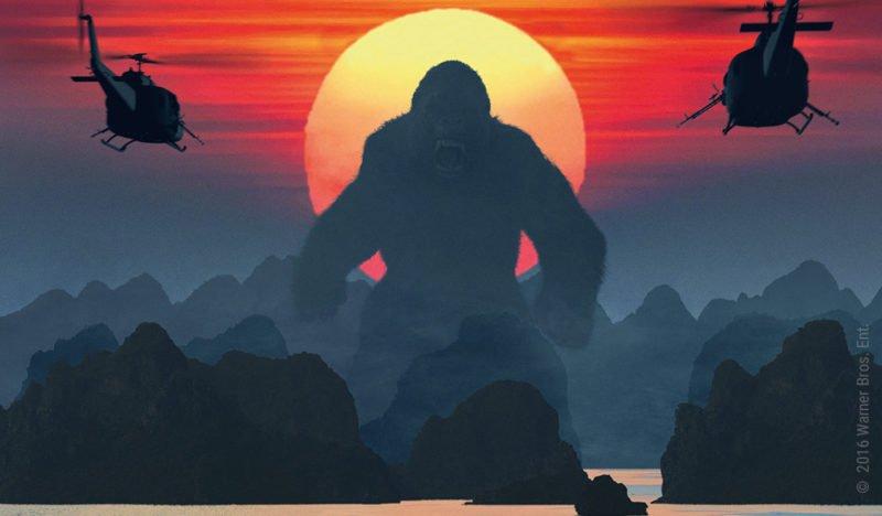 Kong steht vor einem roten Sonnenuntergang während zwei Helikopter ihn angreifen im Film Skull Island