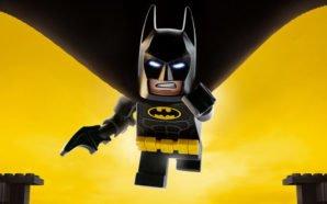 Die Lego Figur Batman fliegt vor einem gelben Hintergrund siegessicher der Kamera entgegen