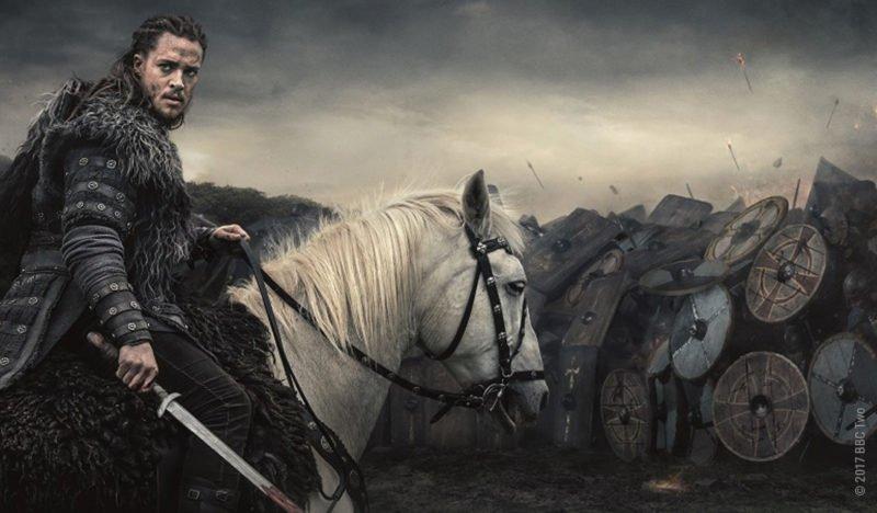 Uhtred sitzt auf einem weiten Pferd vor dem Schildwall einer Armee und dreht sich um