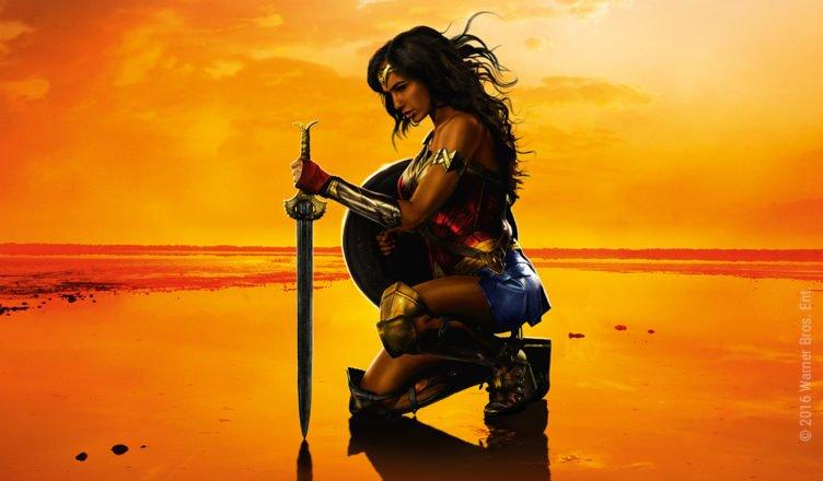 Gal Gadot kniet in voller Rüstung als Wonder Woman am Strand