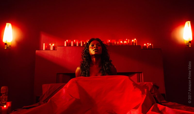 Bilquis der Göttin der Liebe sitzt in einem Bett in einem roterleuchteten Raum in American Gods Staffel 1