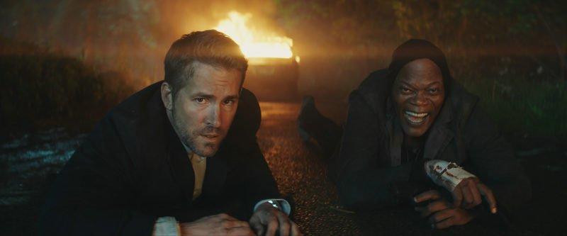 Ryan Reynolds und Samuel L. Jackson auf einer Straße in Szenenbild von Kritik Killer's Bodyguard