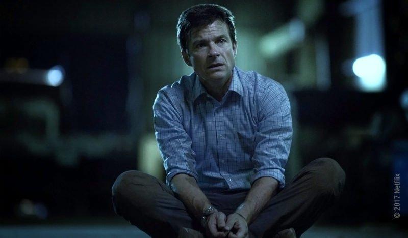 Jason Bateman sitzt mit gefesselten Händen im Schneidersitz am Boden in der Netflix-Serie Ozark – Staffel 1