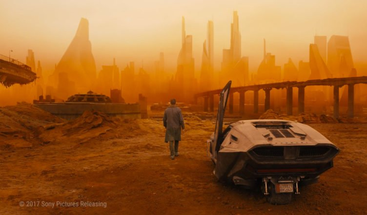 Blade Runner K steht neben einem Auto und starrt auf die rot-gelbe Skyline einer Mega City mit vielen Hochäusern.