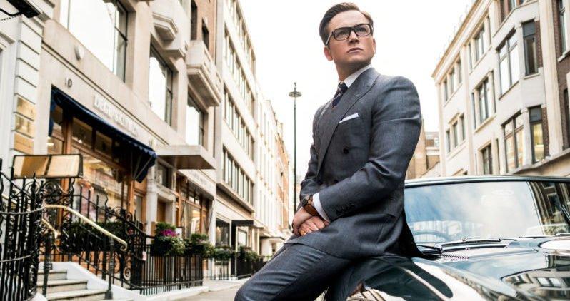 Ein Szenenbild für die Kritik Kingsman The Golden Circle mit Taron Egerton als Eggsy, angelehnt an ein Auto auf einer Straße in London