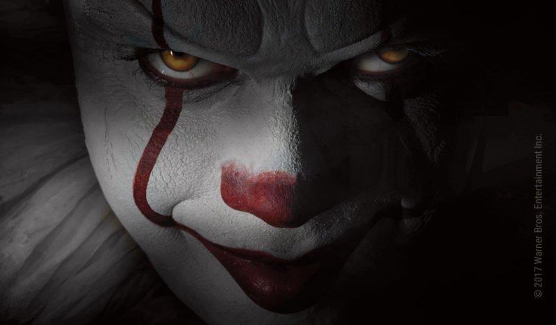 Der geschminkte Grusel-Clown Pennywise lächelt in einer Nahaufnahme bösartige in die Kamera
