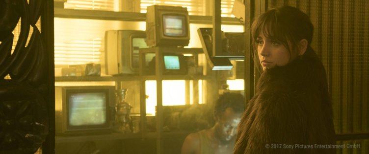 Ana De Armas ist als Replikantin Joi in einem staubigem Raum mit alten TV-Geräten.jpg
