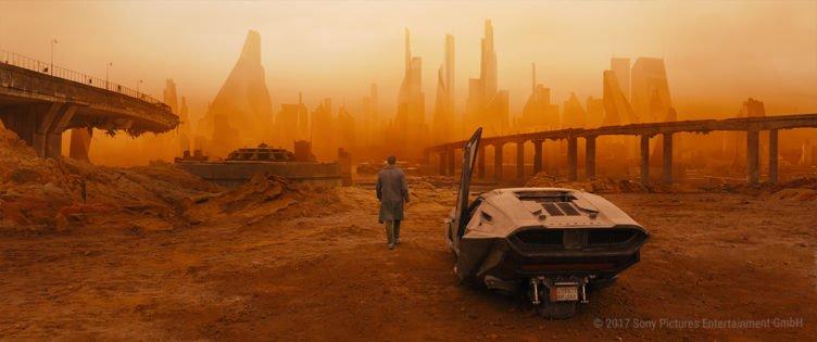 Blade Runner K steht neben einem Auto und starrt auf die rot-gelbe Skyline einer Mega City mit vielen Hochäusern