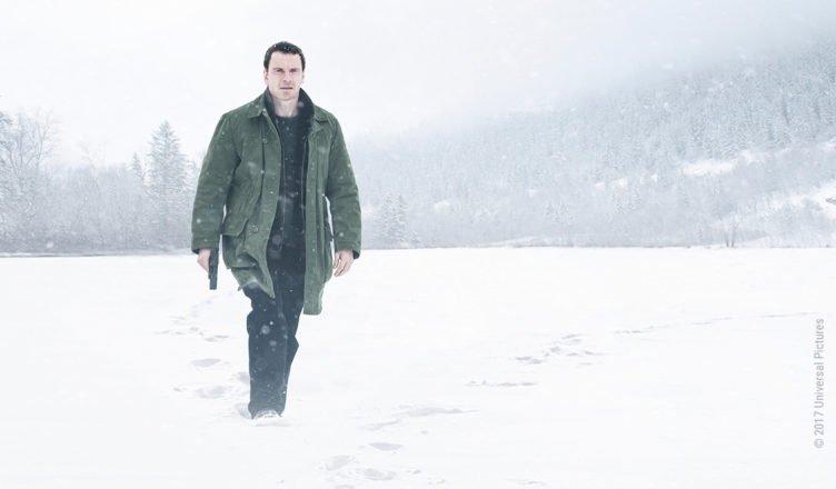 In der Rolle des Kommissar Harry Hole watet Michael Fassbender mit einer Pistole bewaffnet durch tiefen Schnee in Schneemann 2017