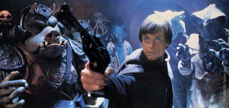 Luke Skywalker zielt mit einer Pistole während er von tierähnlichen Außerirdischen umgeben ist