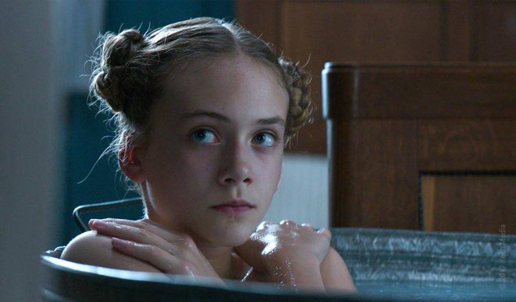 Emilia Jones sitzt als junge Liz schamvoll in einer Badewanne in Brimstone