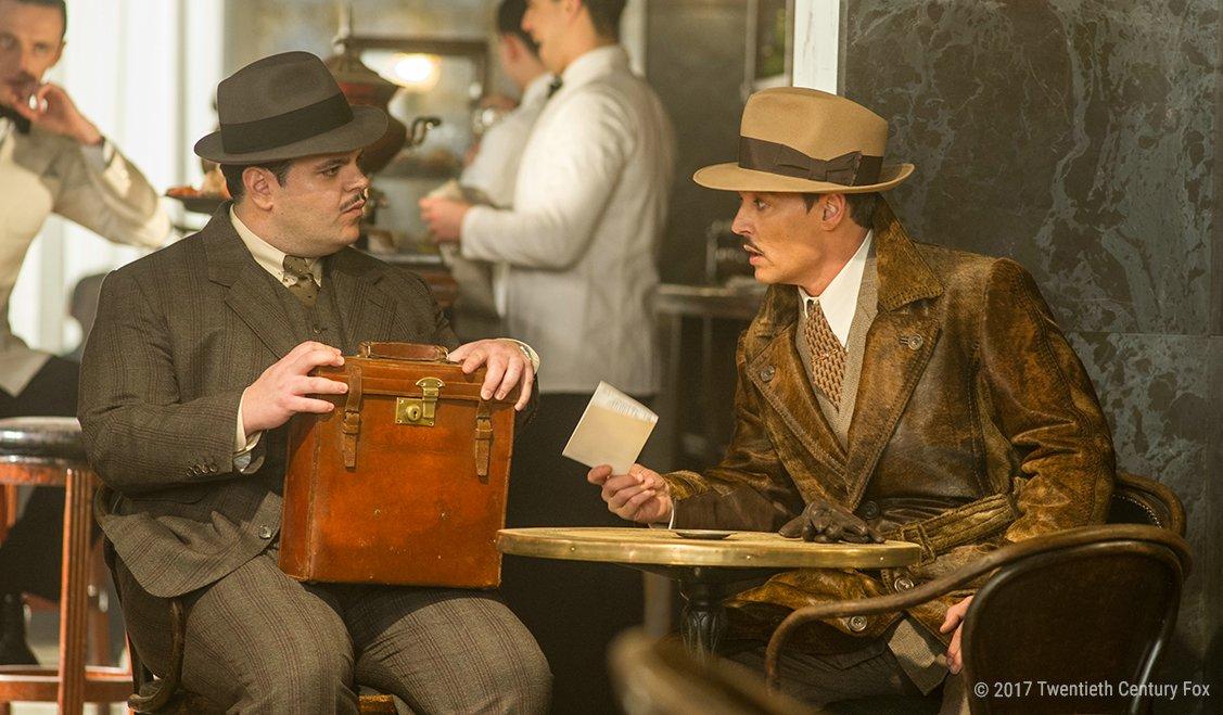 Josh Gad und Johnny Depp unterhalten sich in einem Zugabteil in einem Szenenbild für Kritik Mord im Orient Express