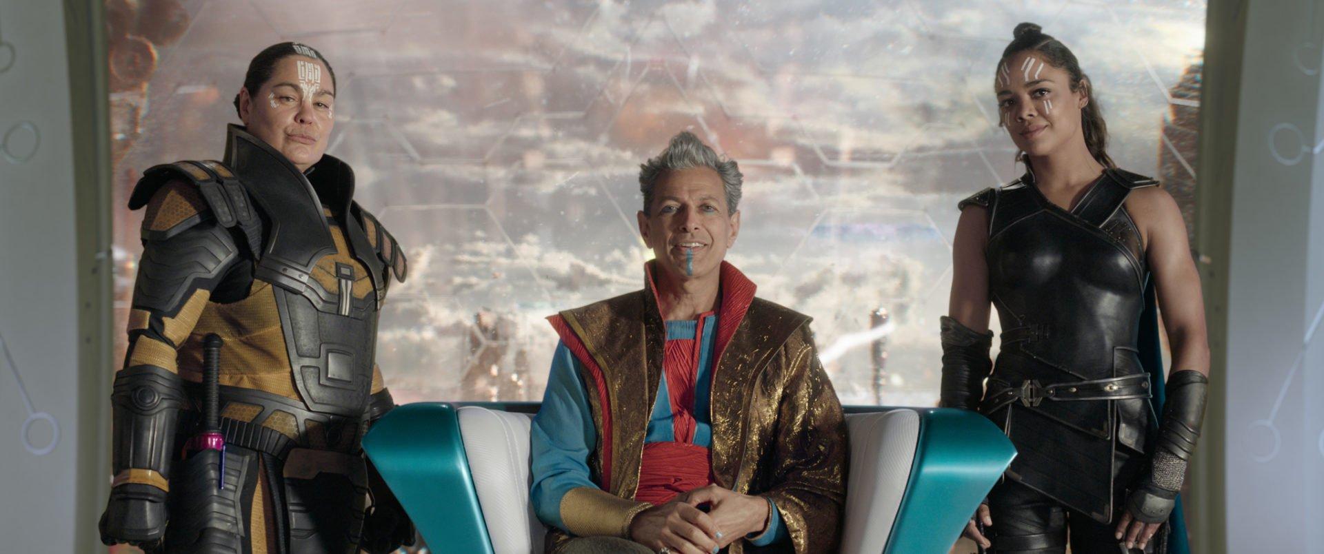 Topaz (Rachel House), Grandmaster (Jeff Goldblum) und Valkyrie (Tessa Thompson) in einer Reihe vor einer Glaswand in einem Szenenbild für die Kritik Thor Tag der Entscheidung
