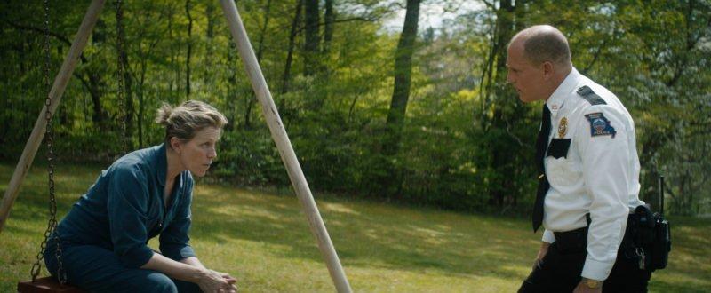Frances McDormand sitzt auf einer Schaukel, ihr gegenüber steht Woody Harrelson in Polizeiuniform