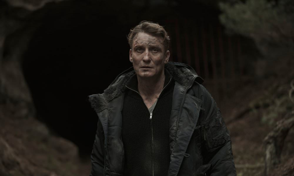 Oliver Masucci als Ullrich vor einer Höhle im Wald in einem Szenenbild der Netflix Serie Dark
