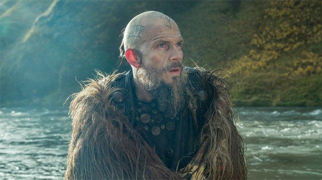 Gustaf Skarsgård als Floki steht vor einem Wasserfall in Island in einem Szenenbild für Kritik Vikings Staffel 5 Teil 1
