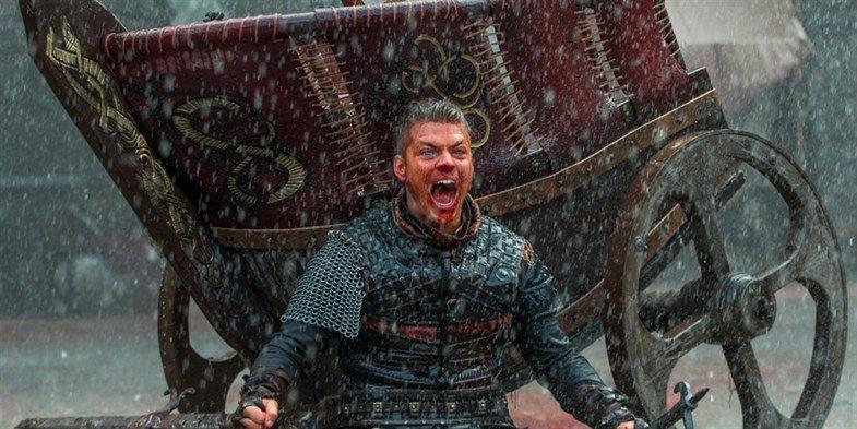 Ivar sitzt vor einer Schlachtkutsche mit blutverschmiertem Gesicht bei Regen auf einem Schlachtfeld in einem Szenenbild für Vikings Staffel 5 Folge 3 Heimatland