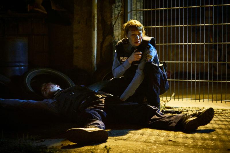 Ein Szenenbild für Kritik Nur Gott kann mich richten mit Minichmayr als Polizistin Diana, mit einem Mikrofon auf dem Boden kauernd