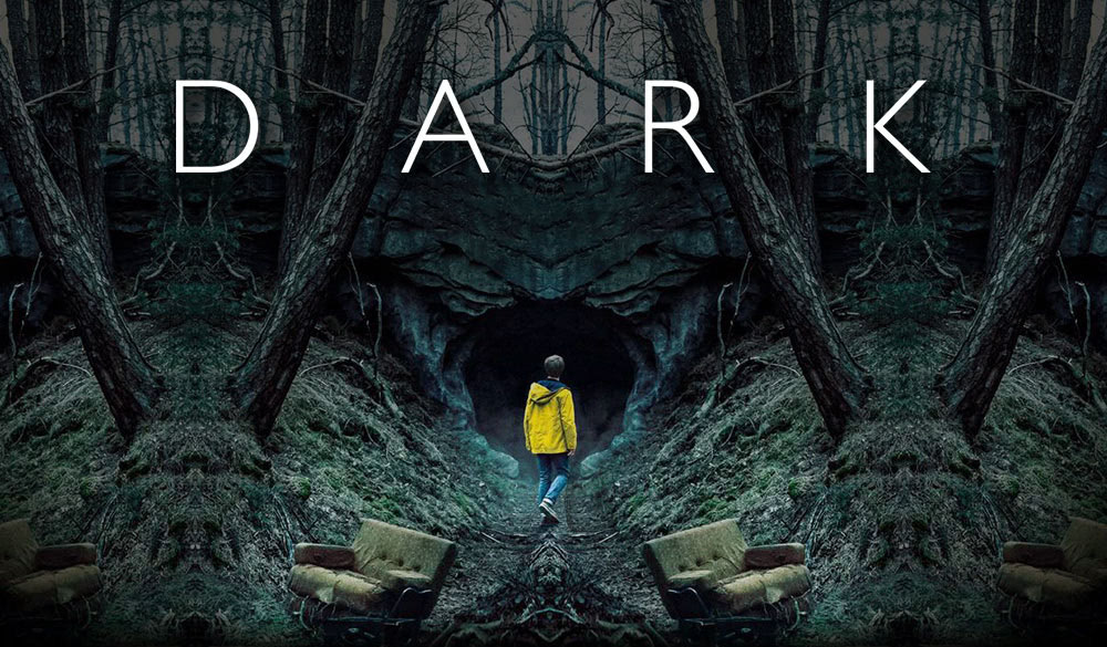 Jonas Kahnwald steht in einer gelben Regenjacke vor einer Höhle in Winden in Dark – Staffel 1