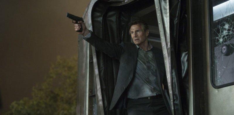 Liam Neeson steht an einer Zugtür und zielt mit einer Pistole in einem Szenenbild für Kritik The Commuter