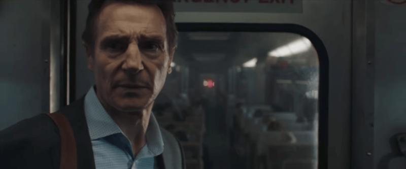 Liam Neeson steht vor einem Zugabteil in Szenenbild für Kritik The Commuter