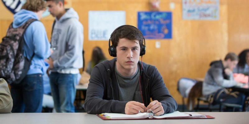 Dylan Minnette als Clay sitzt in einem Klassenzimmer und trägt Kopfhörer in einem Szenenbild für Kritik Tote Mädchen lügen nicht Staffel 1