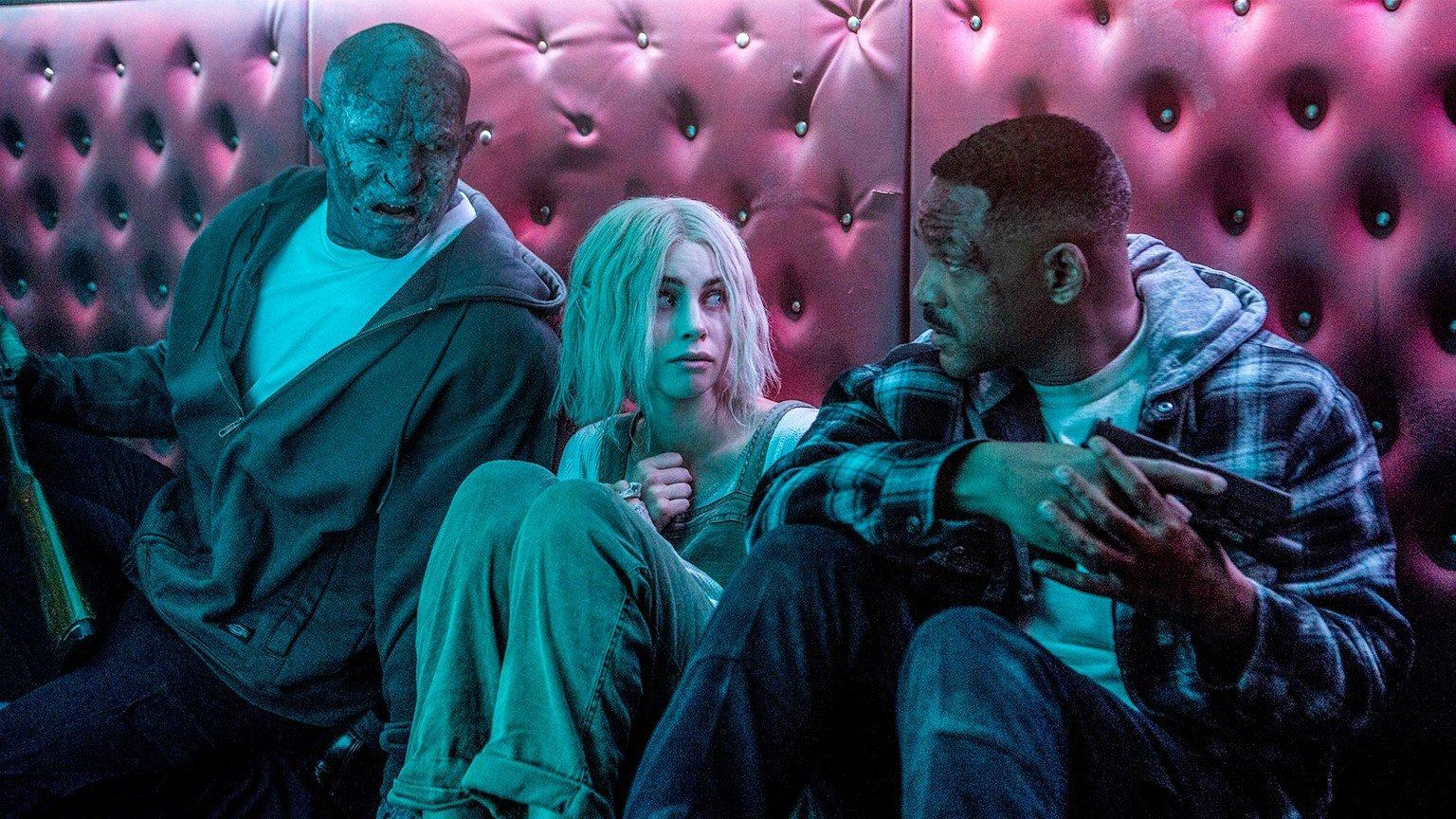 Joel Edgerton als Ork, Lucy Fry und Will Smith sitzen an einer Wand angelehnt in einem Szenenbild für Kritik Bright von Netflix