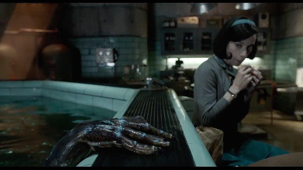 Elisa (Sally Jankins) macht eine Mittagspause neben einem dunklen Becken, aus welchem die Hand eines Wasserwesens (Doug Jones) ragt. Ein Szenenbild für Kritik Shape of Water – Das Flüstern des Wassers