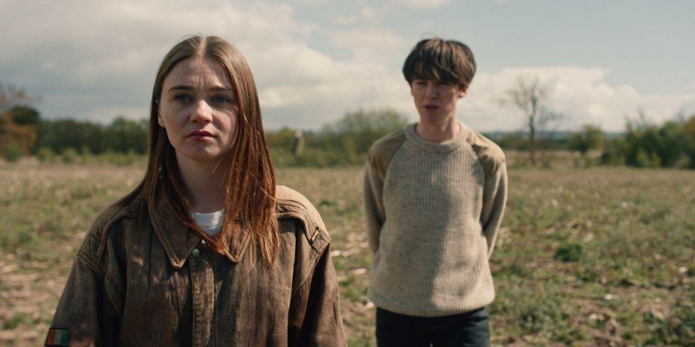 Jessica Barden und Alex Lawther stehen auf einer Wiese in Szenenbild für Kritik The End Of The F***cking World