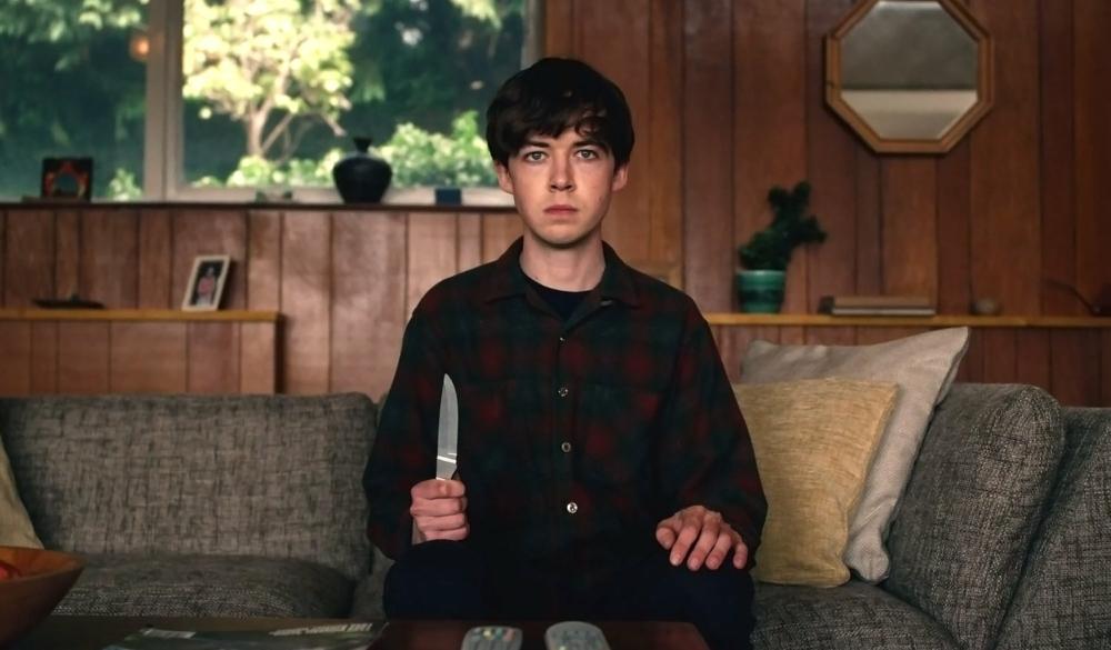 Alex Lawther sitzt auf einem Sofa und hält ein Messer in der Hand im Titelbild für die Kritik The End Of The F***cking World