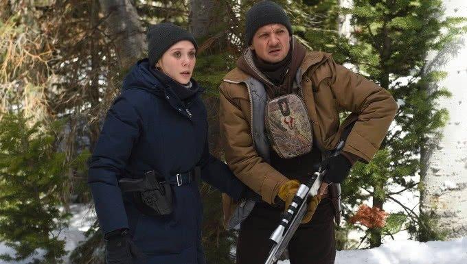 Elizabeth Olson und Jeremy Renner stehen in einem schneebedeckten Wald in einem Szenenbild für Kritik Wind River