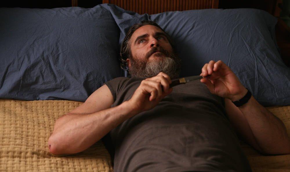 Joaquin Phoenix liegt auf einem Bett mit einem Messer in der Hand in einem Szenenbild für Kritik A Beautiful Day