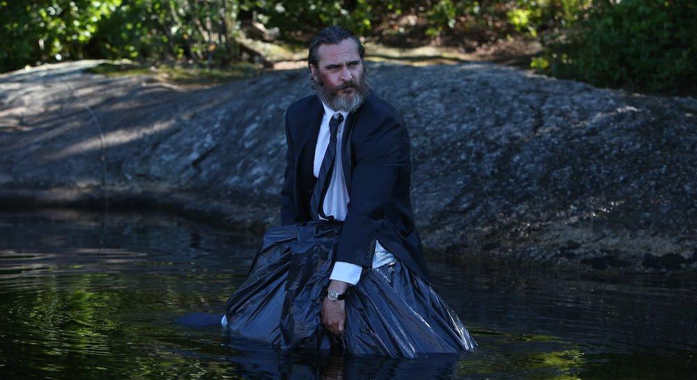 Joaquin Phoenix lässt einen Leichensack im See verschwinden in einem Szenenbild für Kritik A Beautiful Day